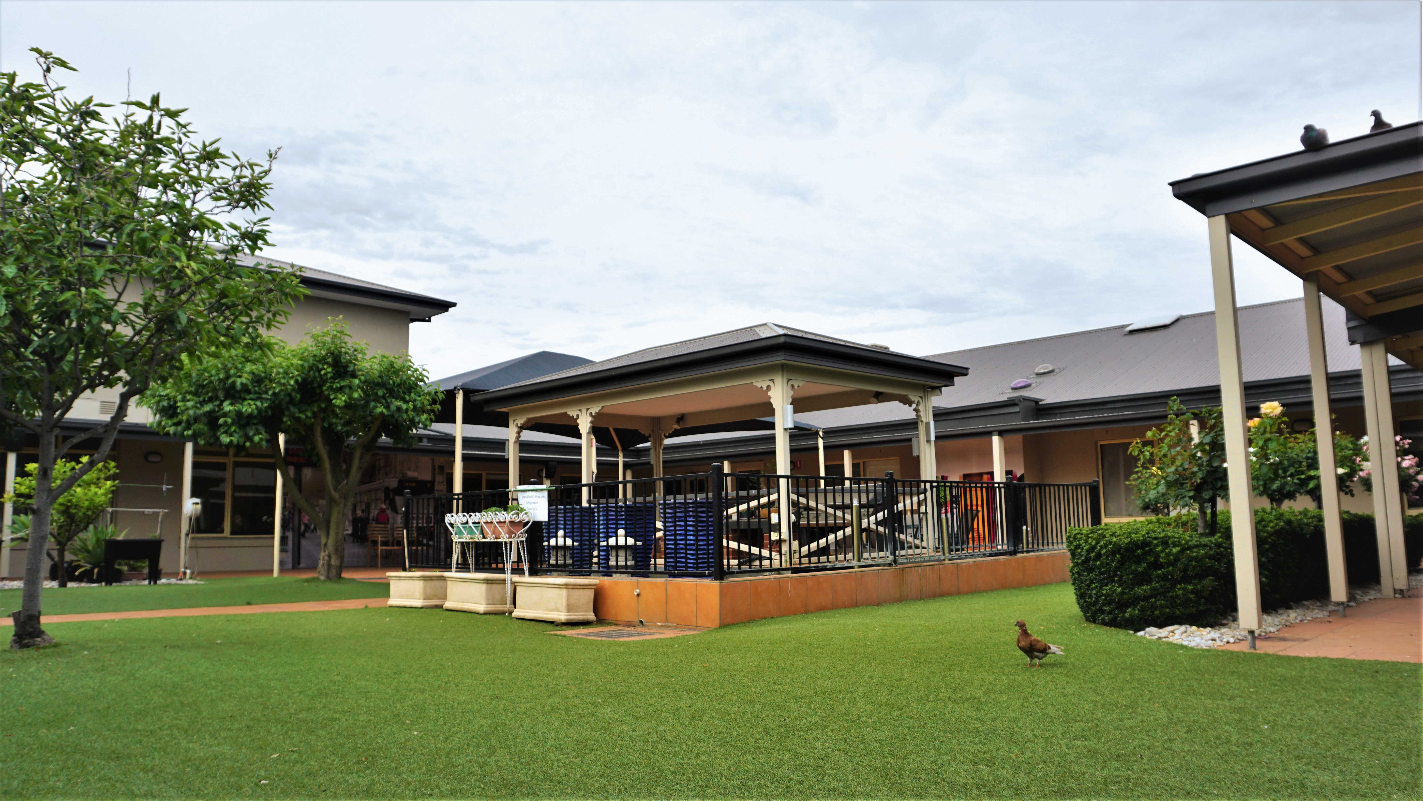 Anzac Lodge Nursing Home, Coburg North VIC 3058 - Courtyard with BBQ facilities, dementia murals, fruit and vegie planter boxes, pond and pigeon feeding